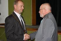 Ustavující zasedání zastupitelstva v Orlové zvolilo starostu Tomáše Kuču. Na snímku mu funkci předává jeho otec Jaromír.