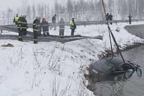 Vytahování havarovaného BMW z rybníka.