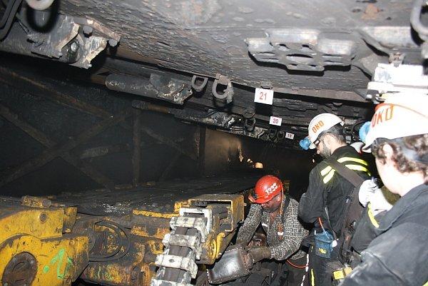 Pracující horníky idrahé zařízení chrání mohutné výztuže. Po jejich posunutí se za nimi vše bortí.