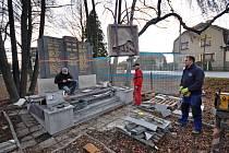Dělníci dokončují instalaci posledních prvků opraveného památníku válečným obětem.