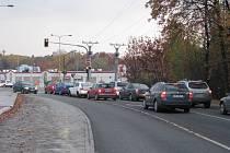 Před světelnou křižovatkou se vytvářejí dlouhé kolony automobilů.