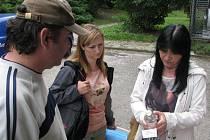 Hygieničky si prohlížejí láhev s podezřelým alkoholem.
