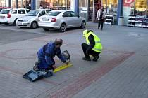 Pracovníci stavební firmy odstraňují nebezpečné zarážky před prodejnou.