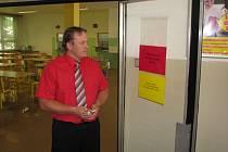 Ředitel ZŠ Fr. Hrubína Tomáš Ptáček stojí u vchodu do školní jídelny, kde v době výdeje stravy stojí zaměstnanec školy.