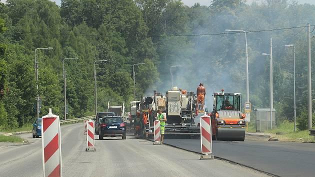 Silničáři pokládají nový asfalt asi na kilometrovém úseku silnice I/59 mezi Dolem ČSA a kostelem sv. Petra z Alkantary. Červenec 2021.