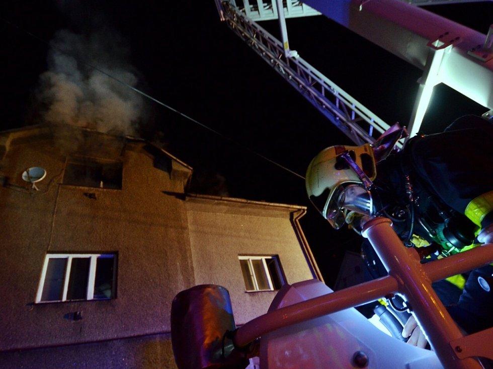 Hasiči při hašení požáru domu v Petřvaldě.
