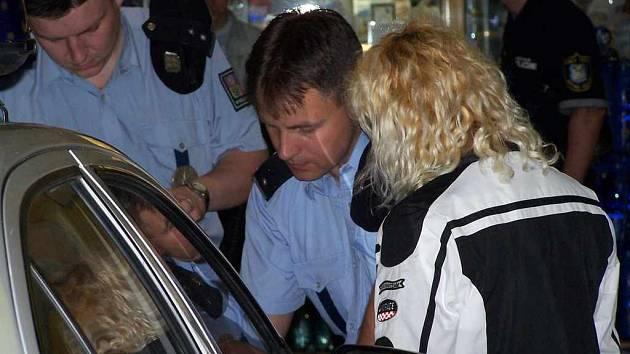 Policisté si opisují údaje z průkazu totožnosti ženy, kterou během páteční akce kontrolovali v ulicích města.