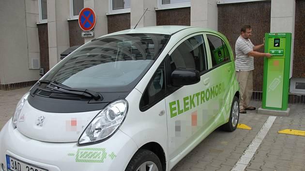 Elektromobil a dobíjecí stanice.