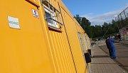 Žluté stavební buňky slouží jako zástupná správní budova s šatnami a kabinami pro rozhodčí.