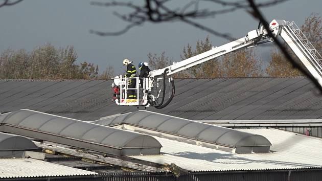 Vyšetřovatelé při zkoumání střechy, kterou se propadl jejich kolega.