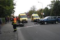 Následky srážky osobního auta s motocyklem.