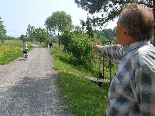 Zahrádkář Jan Kočica ukazuje na prašný úsek ulice Bažantnice, který tamním lidem způsobuje velké problémy.