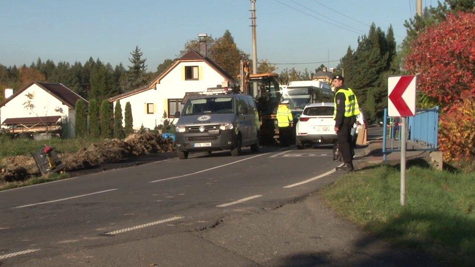 Policejní vozidlo narazilo čelně do lžíce traktorového bagru.
