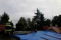 Hasiči při opravě střechy stržené větrem.