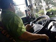 Řidič autobusu za jízdy telefonuje.