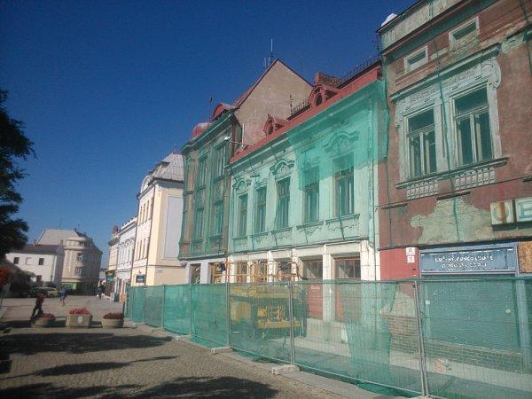 Tři historické domy na Masarykově náměstí vKarviné. dávající omítkou.