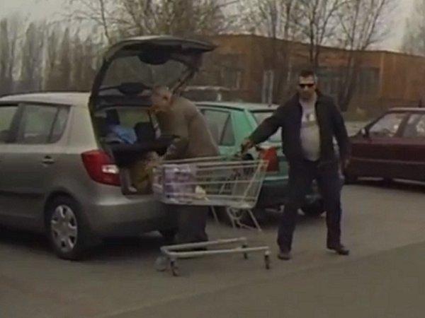 Zloděj krade kabelku znákupního vozíku.
