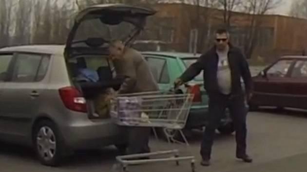 Zloděj krade kabelku z nákupního vozíku.