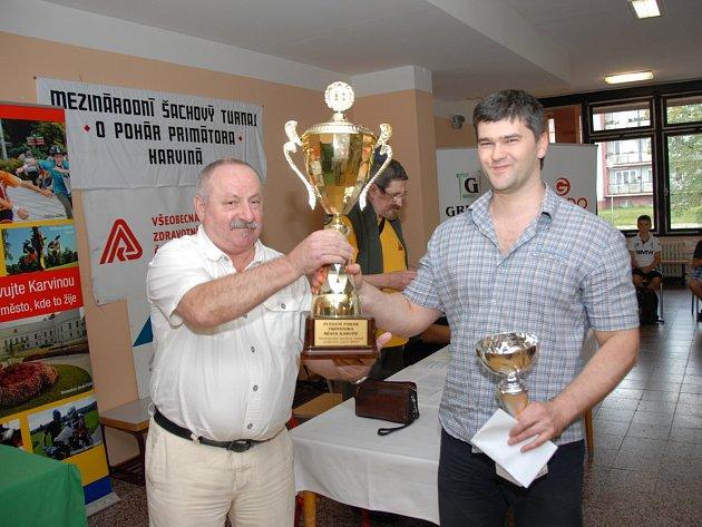 Ředitel mezinárodního šachového turnaje Jaromír Canibal (vlevo) předává pohár za vítězství Ukrajinci Michajlu Simancevovi.