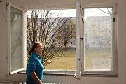 Nájemnice Jana Grácová ukazuje stará dřevěná okna, která už má dnes vyměněna za plastová. .