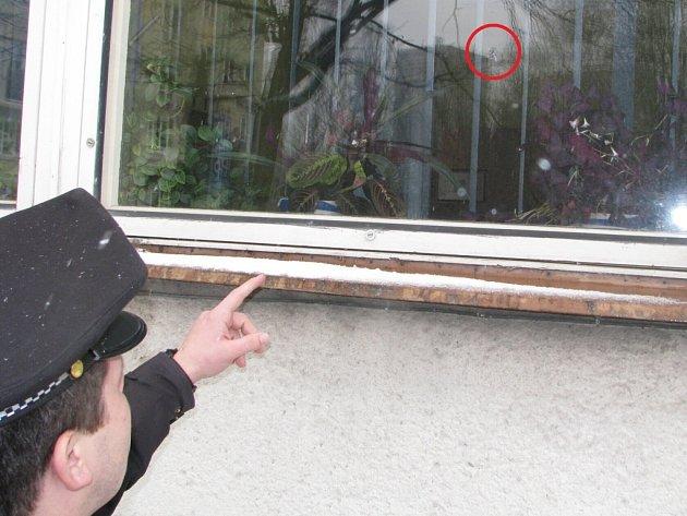 Strážník ukazuje poškozené okno. Místo vstřelu je označeno červeným kroužkem.