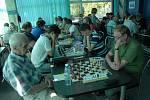 Šachisté různého věku bojují nad šachovnicemi o prvenství v karvinském turnaji.