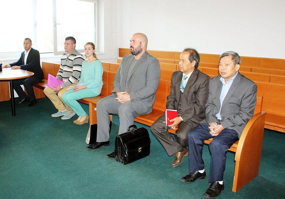 Na lavici obžalovaných. Uprostřed v šedém obleku je Richard Adamus, po jeho levici je tlumočník a zcela vpravo Van Loi Truong.