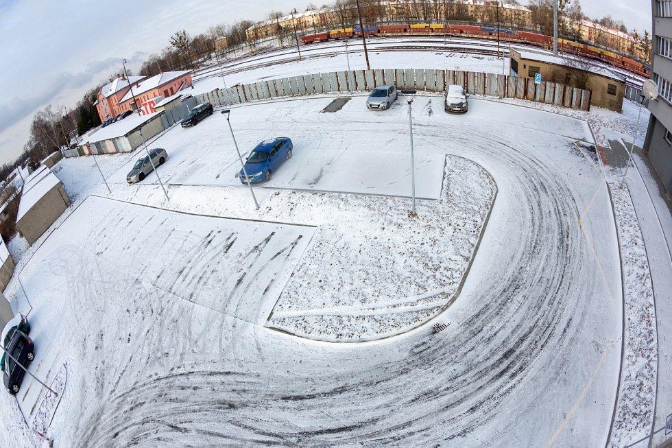 Parkoviště u věžového domu v sousedství železniční stanice v Havířově.