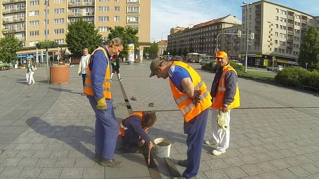 Pracovníci programu Čisté město při úklidu kanalizace na náměstí po bouřce.