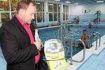 Ředitel školy Tomáš Ptáček ukazuje defibrilátor, který mají k dispozici plavčíci na školním bazéně.
