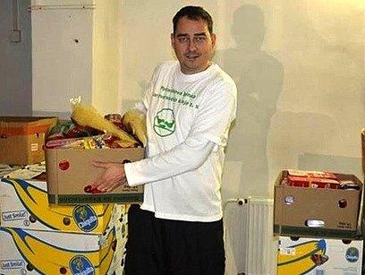 Ředitel potravinové banky Milan Hloušek rovná ve skladu bedny s těstovinami.