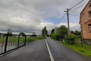 Petřvald, ulice K Pískovně. Vlevo za plotem pozemek, na kterém má stát nová prodejna.