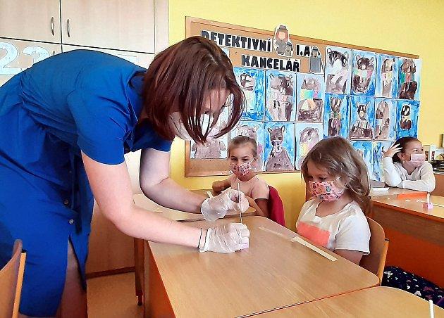 Žáci prvních tříd se vrátili do škol a museli absolvovat antigenní testy. Ty si prováděli sami na asistence učitelky tak jako například v1. Ana ZŠ Dělnická vKarviné.