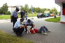Strážníci ošetřují zraněného muže, který byl označen za útočníka.