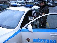 Strážník ukazuje tablet, který je součástí radaru ve služebním vozidle.