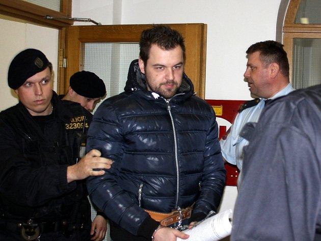 Eskorta přivádí Petra Kramného k soudu.