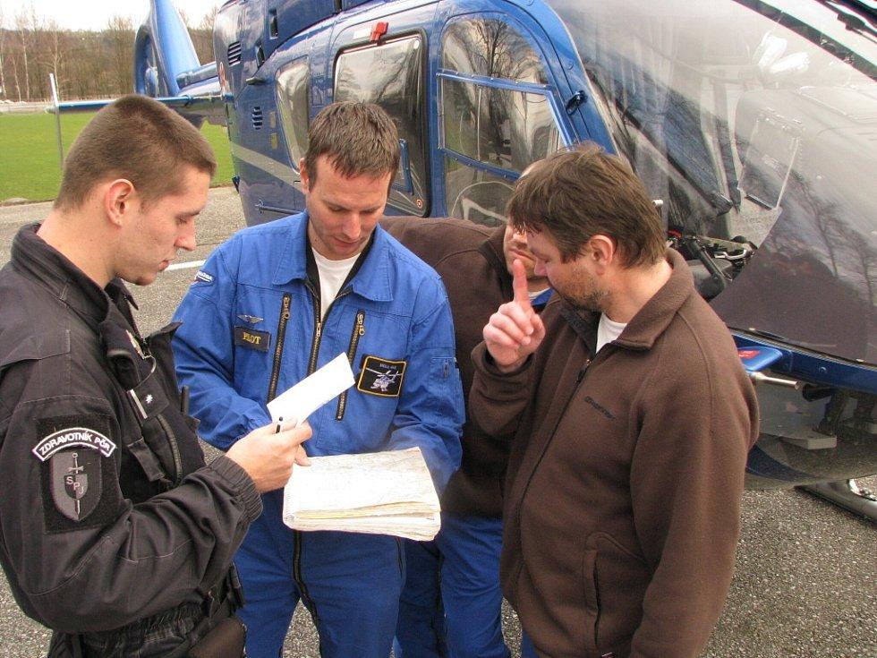 Policisté se domlouvají na postupu pátrání po pohřešované osobě.
