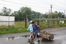 Šrotáci táhnou vozíky do sběrny.