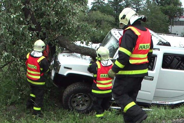 Vyprošťování vozu z větví přeraženého stromu.