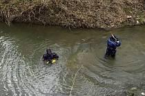 Policisté prohledávali dno řeky Lučiny v Havířově. Potápěč drží nalezený předmět.