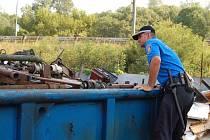 Jeden ze strážníků obhlíží kontejner s železným šrotem, zda v hromadě nazahléhne věc, která mohla být ukradena.