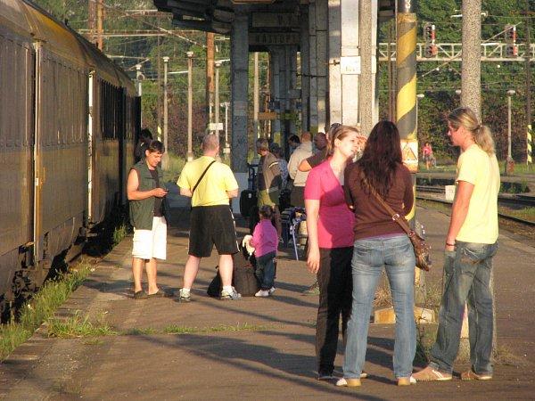 Stevardka RegioJetu vysvětluje cestujícím důvody zpoždění a nabízí občerstvení ve vlaku.