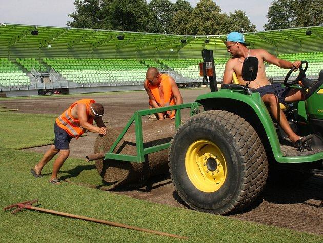 Stavba nového fotbalového stadionu v Karviné finišuje. Kromě dokončovacích prací vně i před areálem dělníci pokládají nový trávník na hřiště.