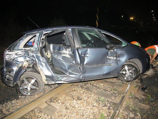 Následky srážky osobního automobilu slokomotivou nákladního vlaku.