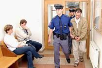 Eskorta přivádí k soudu Romana Lestyana obviněného ze zabití dvou lidí.