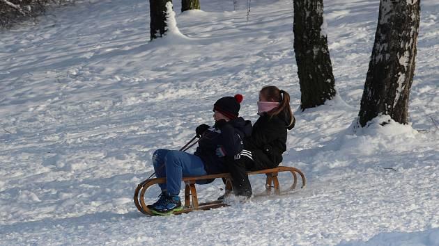 Přívaly sněhu a silný mráz v půli ledna připravila na mnohých místech romantickou zimní podívanou. Sáňkující děti.