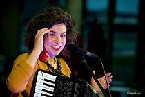 Zpěvačka a hudebnice Kaczi za výlohou kavárny Slivkafé v Karviné.