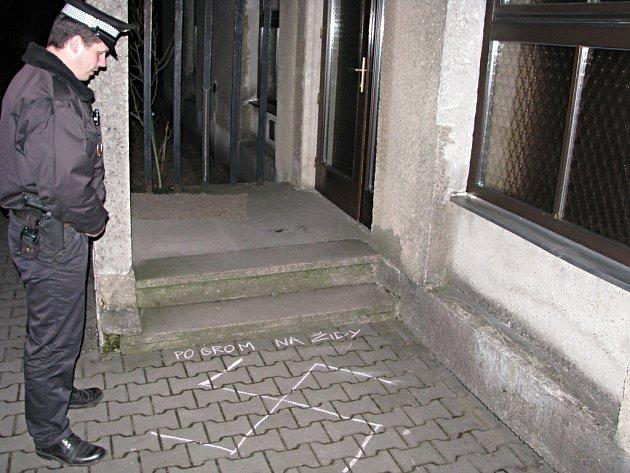 Strážník si prohlíží nápisy a symboly u havířovského kostela.