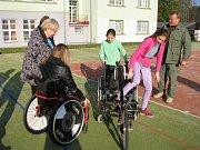 Předání sportovního invalidního vozíku postižené studentce.