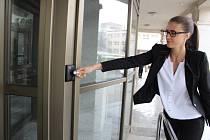 Havířovský magistrát zvyšuje zabezpečení. Mluvčí města Jana Dybová ukazuje, jak si zaměstnanci otevírají dveře radnice.